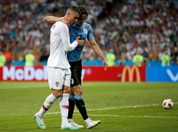 Cavani gjørdi í kvøld størri mun enn Ronaldo í Sochi. Her hjálpur liðformaðurin hjá Portugal skadda tvímálsskjúttanum út av vøllinum (Mynd: EPA)
