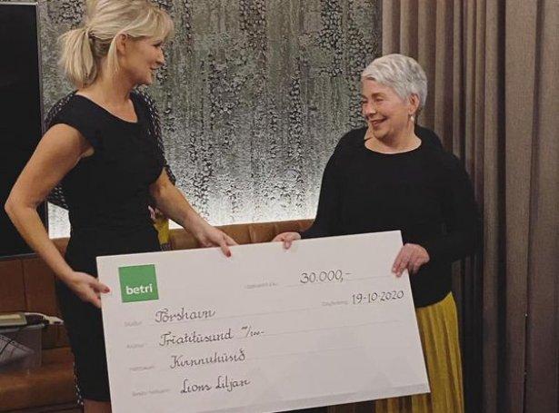 Forsetin í Lions Club Liljan Fía Petersen handar Ann-Britt Fríðheim Mortensen leiðara í Kvinnuhúsinum kekk á 30.000 kr