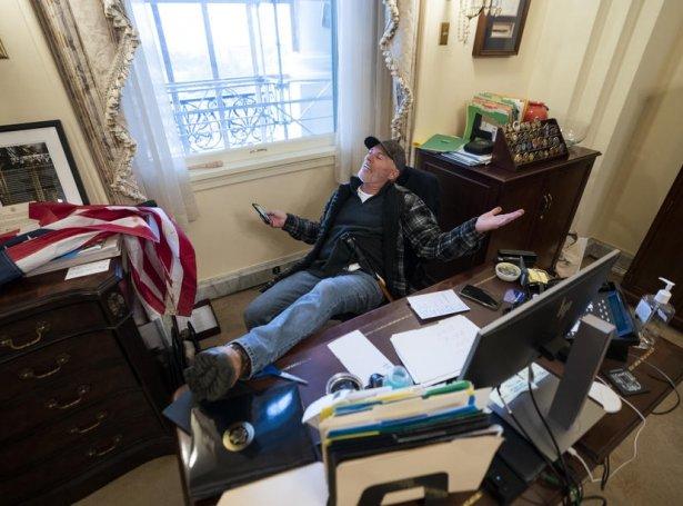 Ein Trump-viðhaldsmaður í stólinum hjá Nancy Pelosi í sjálvari skrivstovuni hjá tingforkvinnuni (Mynd: EPA)